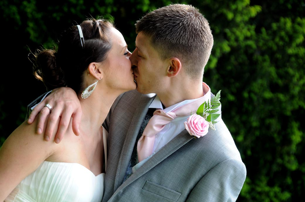 A beautiful romantic wedding couple kiss picture taken at Surrey wedding venue Weybridge Register Office in the garden