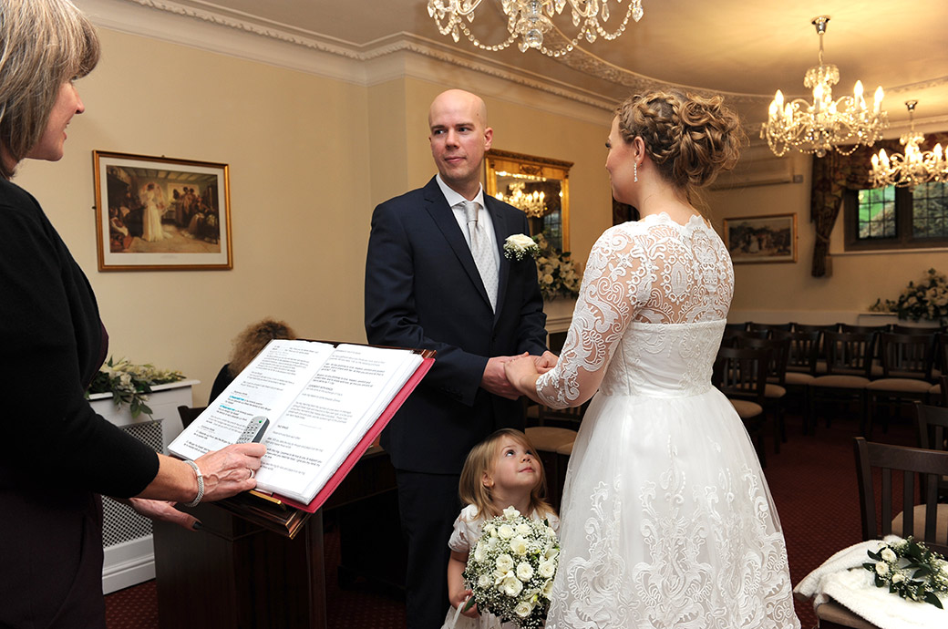 Cute little daughter of the Bride and Groom Surrey at wedding venue Weybridge Register Office looking up to her mummy during the marriage ceremony in the Rylston Suite