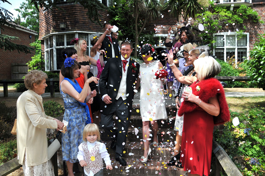 Happy wedding photo of everyone throwing confetti on the the steps in the garden at the back of Weybridge Register Office in Surrey