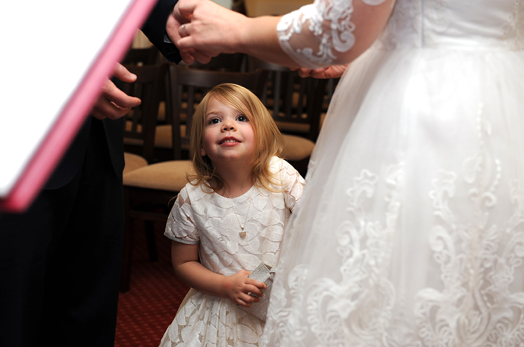 Unusual wedding picture of the Bride and groom's daughter looking up at the exchange of rings above her in the Rylston Suite at Surrey venue Weybridge Register Office