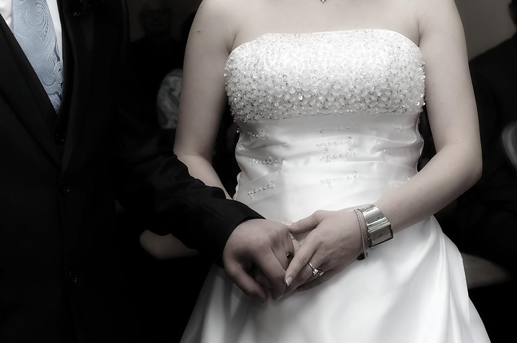 Tender moment captured in this close up wedding picture taken at Weybridge Register Office Surrey of the Bride and groom holding hands during the marriage ceremony
