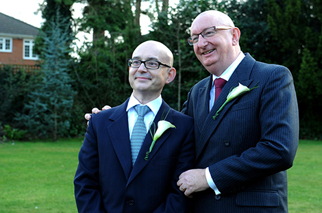 All smiles for a couple of happy Grooms in this delightful wedding photo captured on the garden lawn at Surrey wedding venue Weybridge Register Office