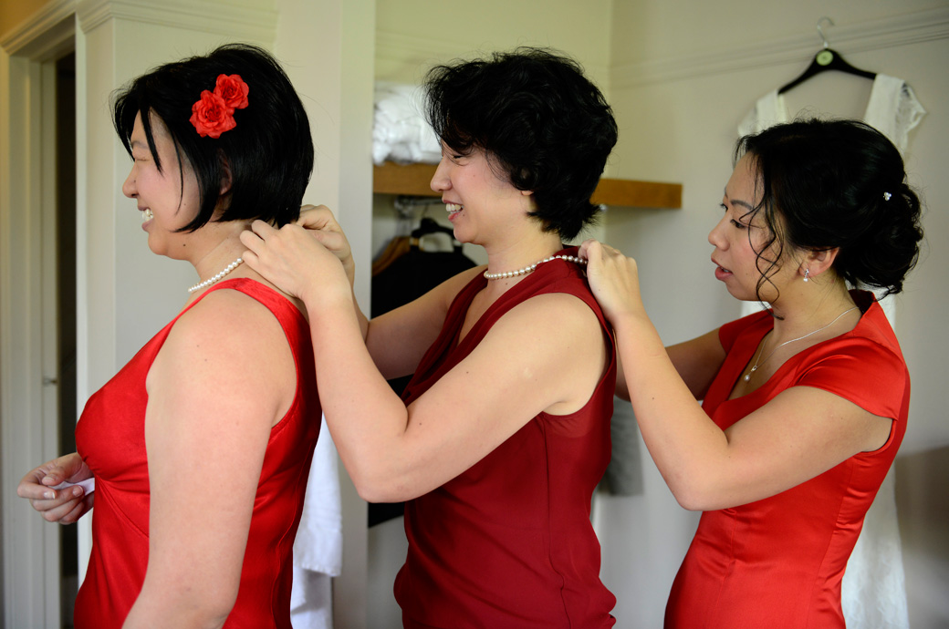 A fun wedding photo of three Bridesmaids putting on necklaces captured by Surrey Lane wedding photographers prior to leaving for  Weybridge Register Office