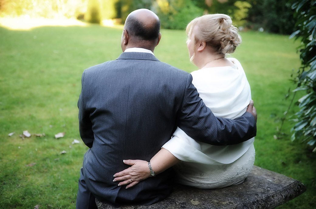 Romantic wedding photograph of a Bride and groom in the garden at Surrey wedding venue Weybridge Register Office taken as they sit on a bench arms around each other