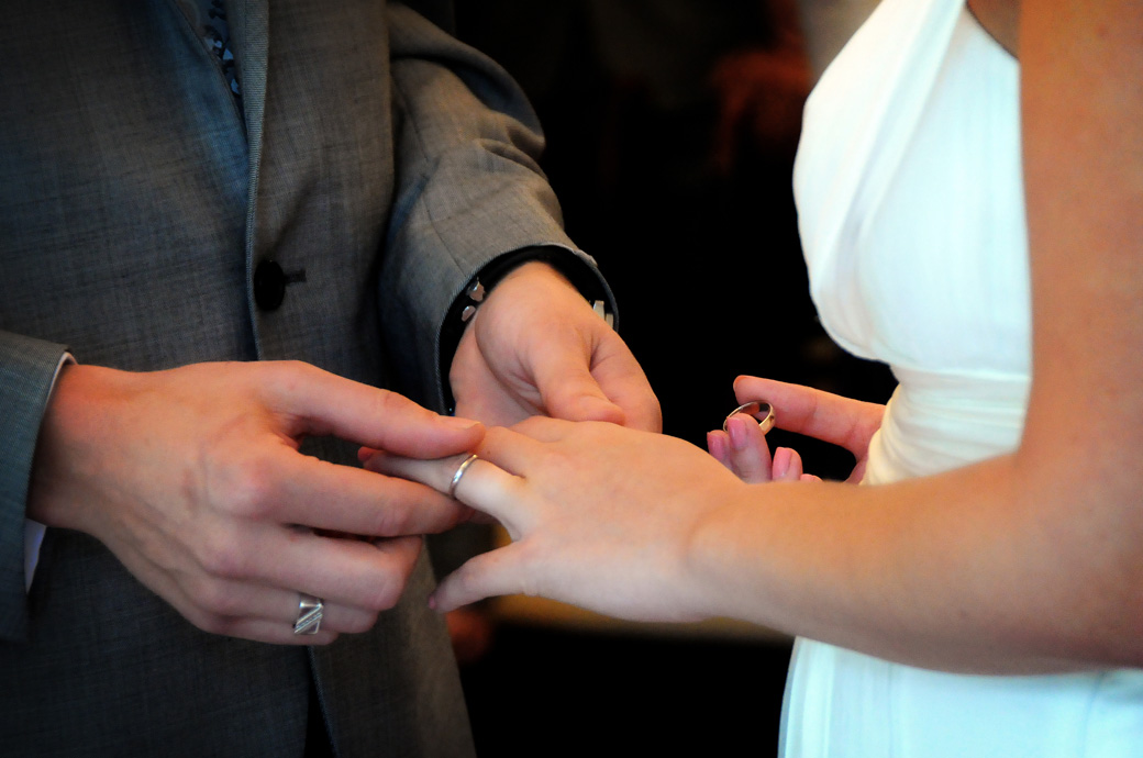 Exchanging of the rings in this intimate close up wedding photograph captured in the Rylston Suite at Surrey wedding venue Weybridge Register Office