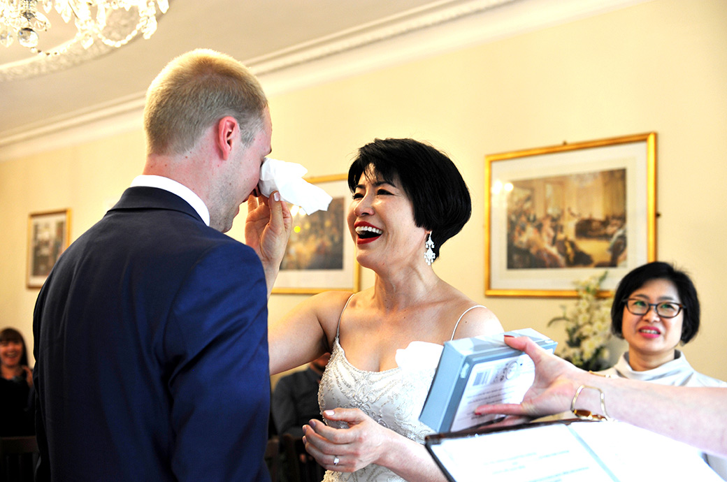 Wedding picture of a loving happy Bride wiping the tears from her Groom's eyes captured in the Rylston Suite at Weybridge Register Office Surrey during the marriage ceremony