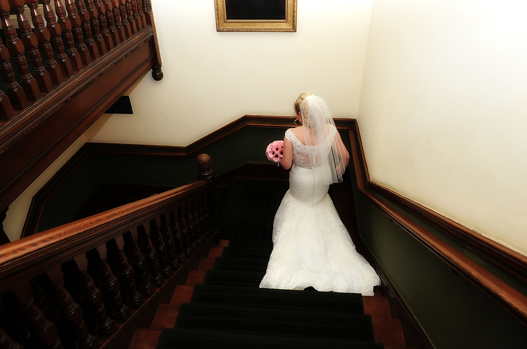 Wedding picture view from above of a Bride holding her bouquet and descending the rich oak staircase at Woodlands Park Hotel Surrey on route the marriage ceremony room
