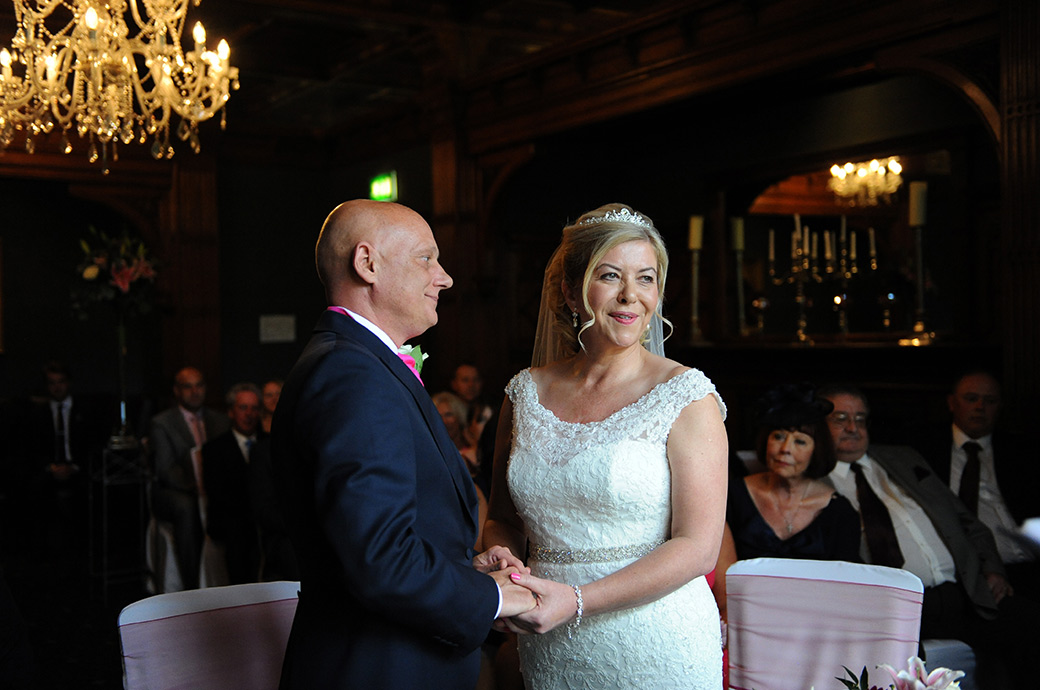 Loving and content faces revealed as the Bride and groom hold hands during their marriage ceremony at Surrey wedding venue Woodlands Park Hotel in The Oak Room