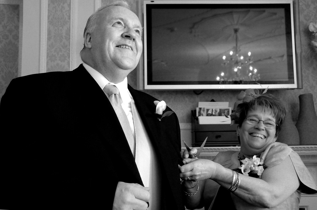 A moment of fun and laughter in this delightful wedding picture of the Bride's mum adjusting her dad's suit at Surrey wedding venue Woodlands Park Hotel