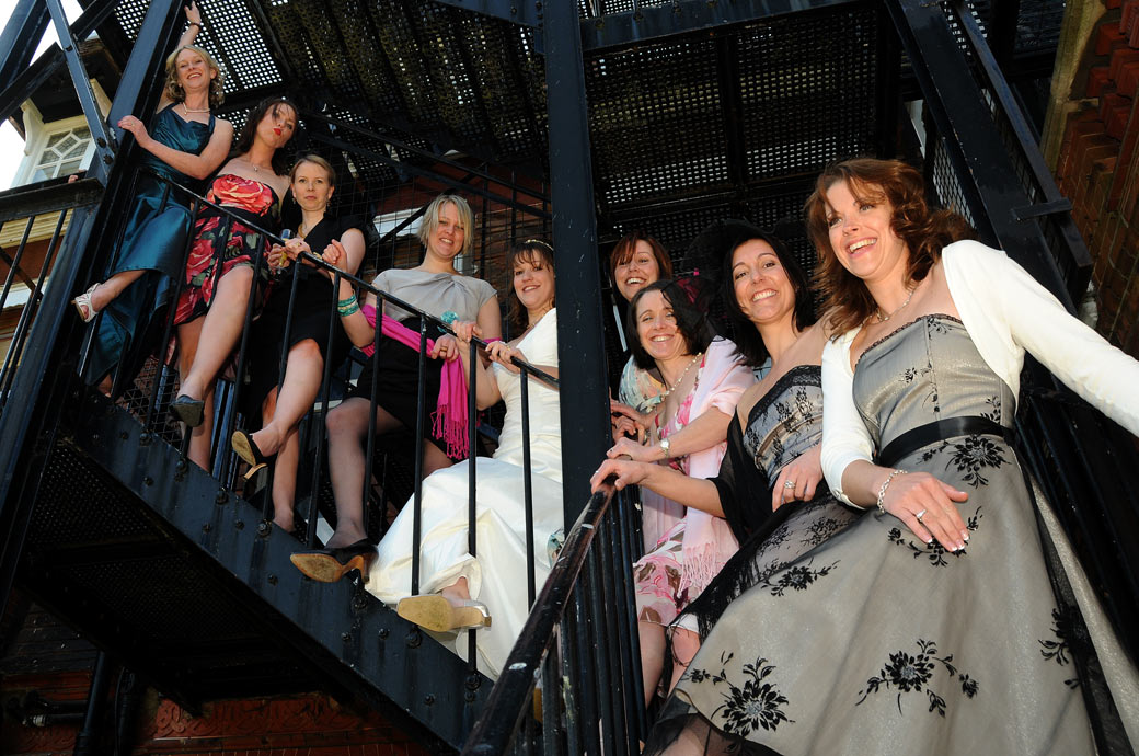 Ladies have fun and shake their legs in this wedding photo taken on the fire escape Woodlands Park Hotel a Victorian Surrey wedding venue in Cobham