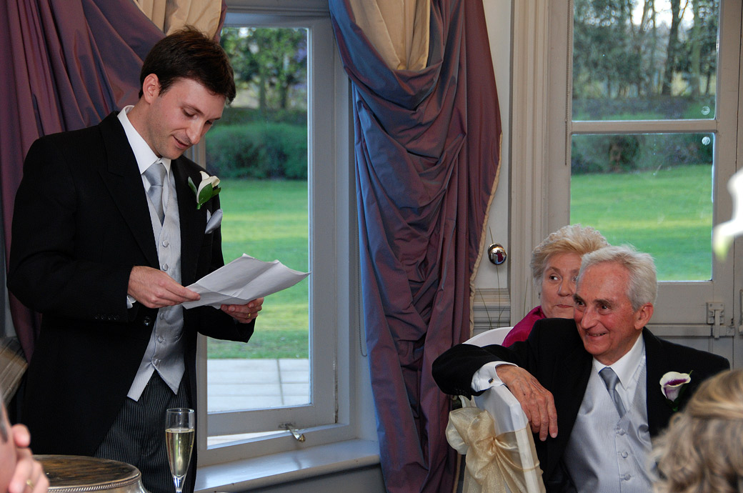 The Best man brings out a smile from his father in this sweet Surrey wedding photograph taken during the speeches at Woodlands Park Hotel in Stoke D'Abernon