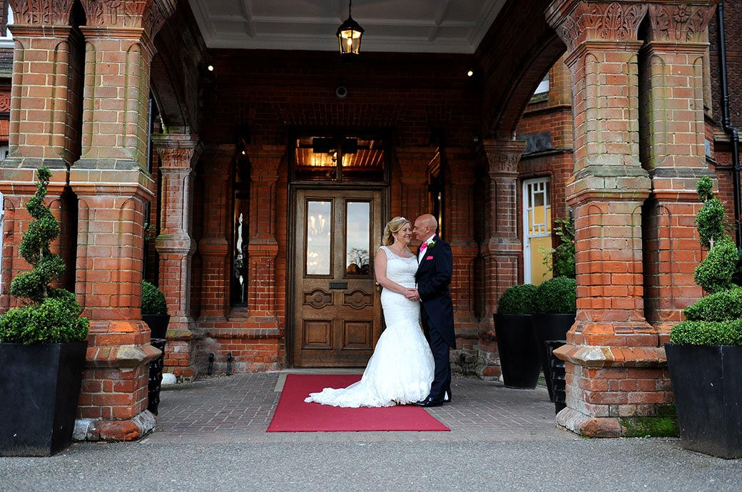 Happy newlyweds striking a romantic pose out on the red carpet at the entrance to the grand Victorian Woodlands Park Hotel a popular wedding venue in leafy Surrey