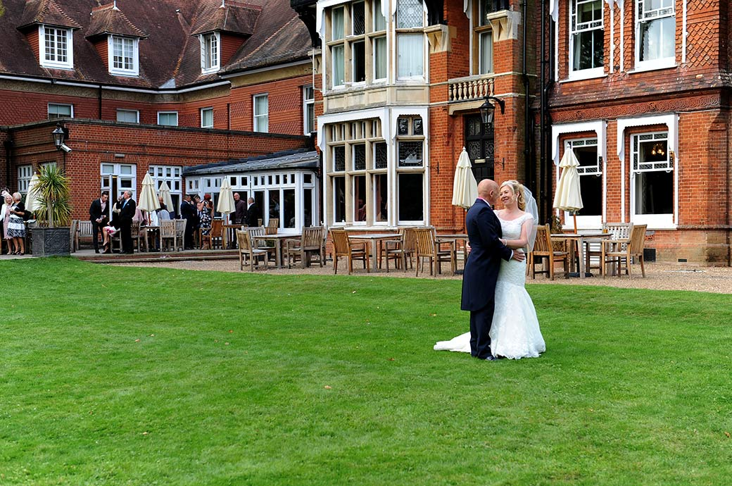 Wedding photograph of loving looks as newlyweds embrace out on the back lawn at the large Victorian Surrey wedding venue Woodlands Park Hotel Stoke D'Abernon Cobham