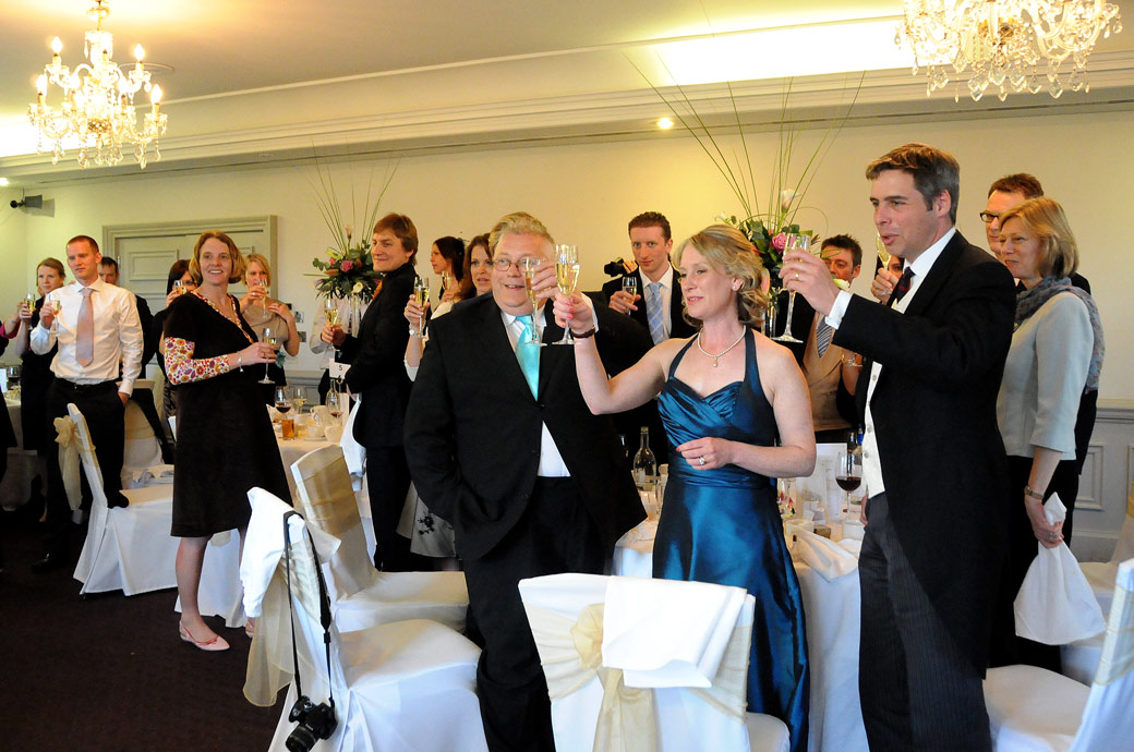 Guests raise their glasses and toast the newly-weds in this wedding picture taken at Surrey wedding venue Woodlands Park Hotel in the Cornwall Suite