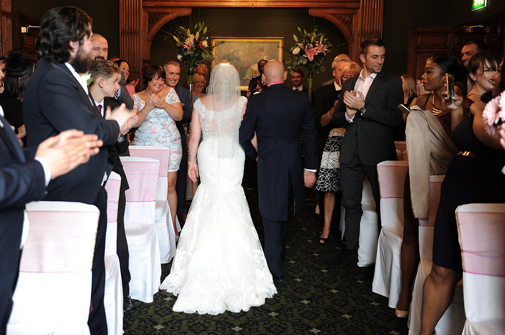 Newlyweds at Woodlands Park Hotel in Surrey walk down the aisle of The Oak Room as husband and wife to loud applause and congratulations from the wedding guests
