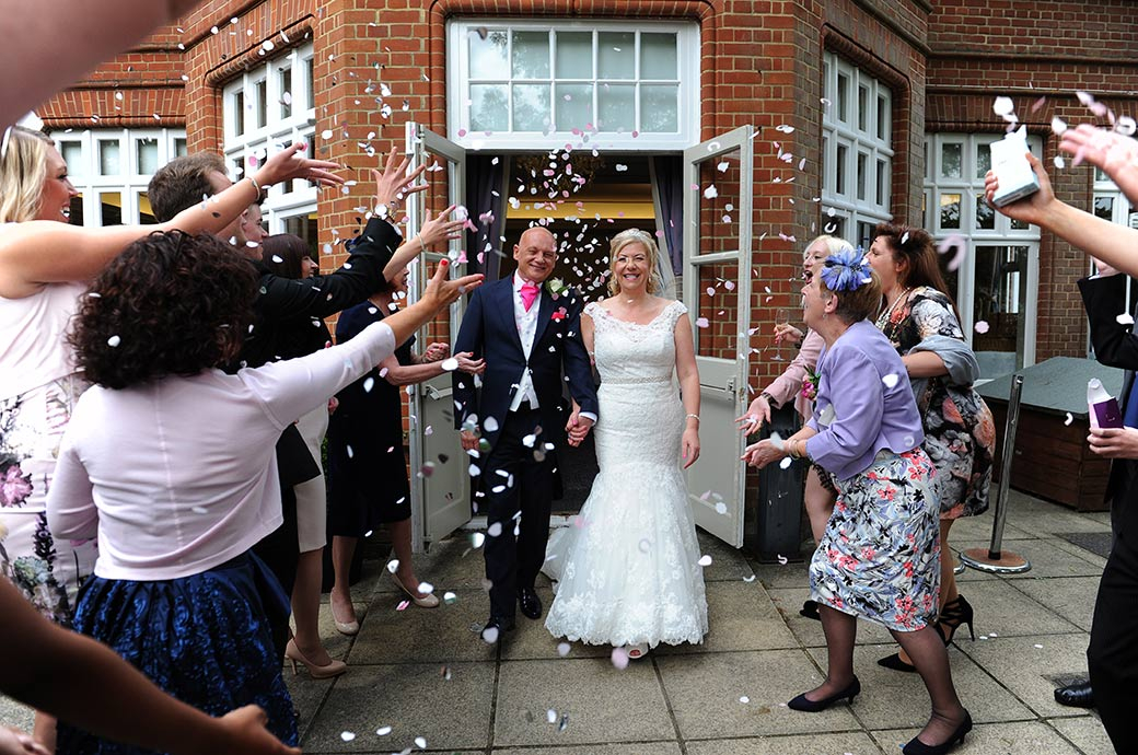 Everyone captured here at the rather special Surrey wedding venue Woodlands Park Hotel in Stoke D'Abernon Surrey out on the terrace throwing confetti over the newlywed couple