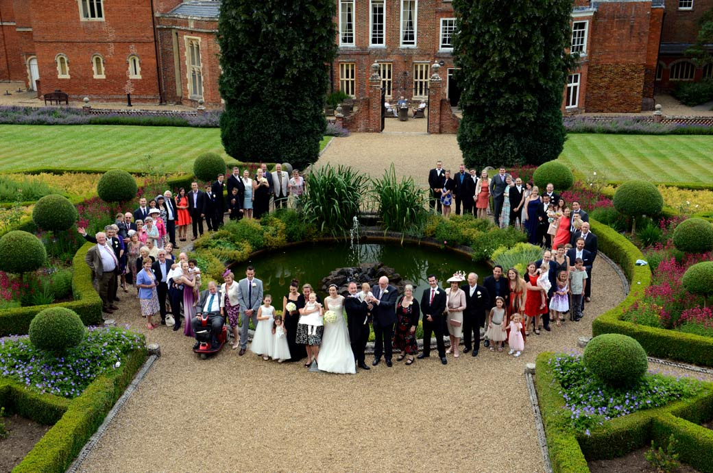 An aeriel group wedding photo of everyone standing around the fountain captured by Surrey Lane wedding photographers at Wotton House Dorking
