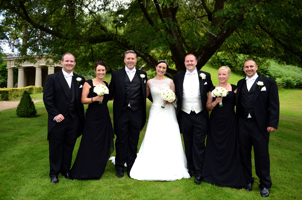 A very smart wedding party in an unusal black and white colour scheme captured in this group wedding photo in the beautiful grounds of Wotton House a lovely Surrey wedding venue