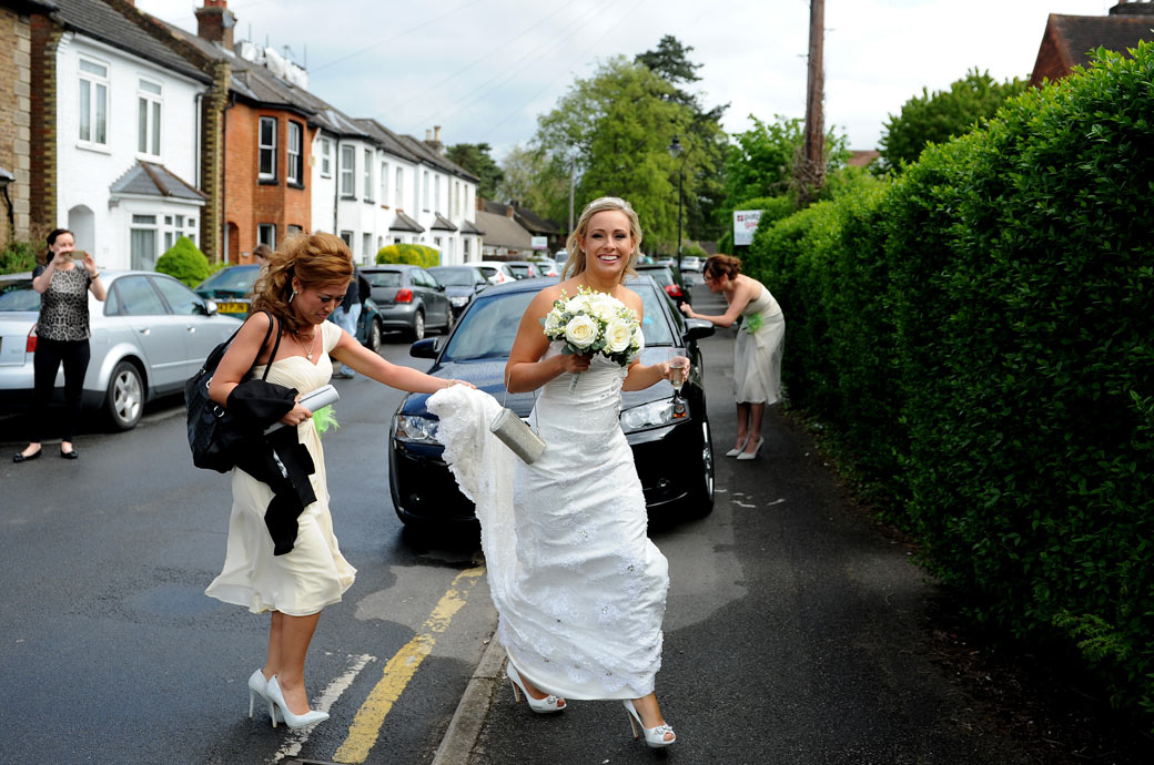 An excited Bride crosses the road from her home to the Bridal car captured in this wedding picture on the way to Surrey wedding venue Wotton House in Dorking