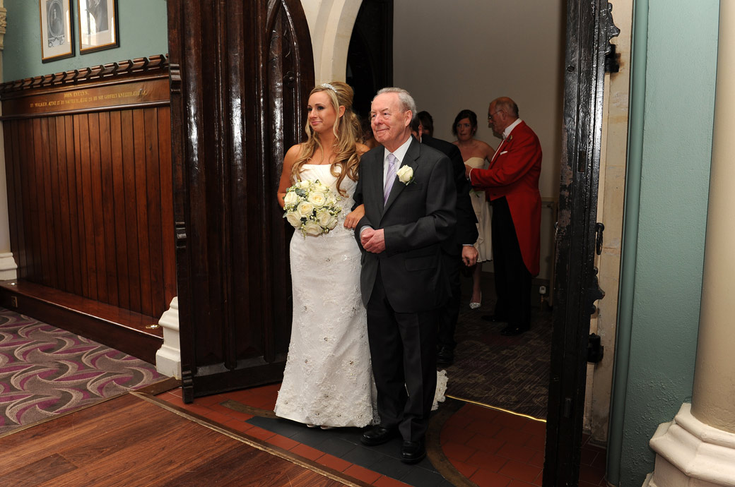 An emotional Bride on the arm of her father captured in this wedding picture taken as they are about to walk down the aisle of the Old Library at Wotton House Dorking in Surrey