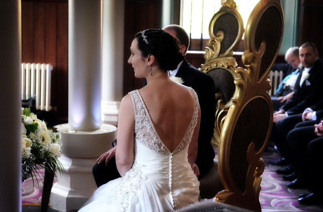 A wedding photo of the back of an elegant Bride taken as she sits on the wedding throne listening to a reading captured at Wotton House a fine Surrey wedding venue