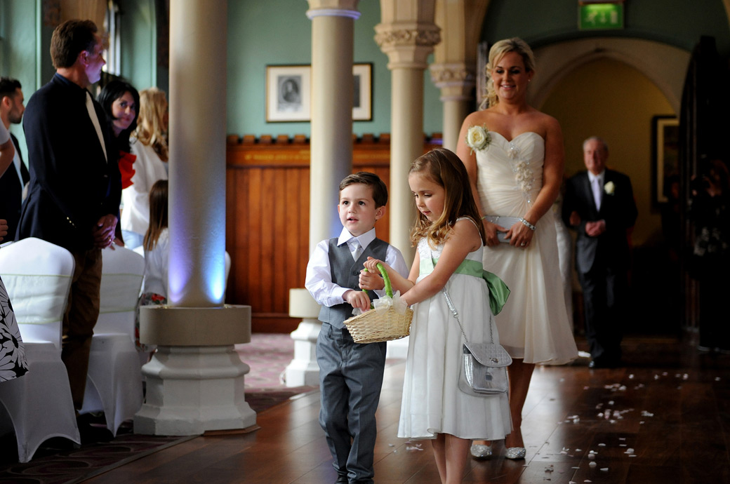 Sweet wedding photograph of the flowergirl and pageboy throwing petals down the aisle of the Old Library as they lead the wedding party in Surrey venue Wotton House
