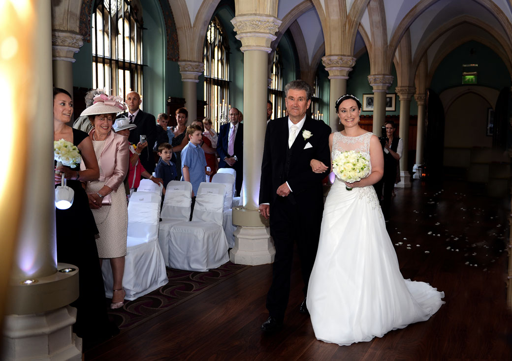 A beaming Bride as she walks down the aisle on the arm of her Father in the lovely Old Library in this wedding photo taken at Surrey wedding venue Wotton House