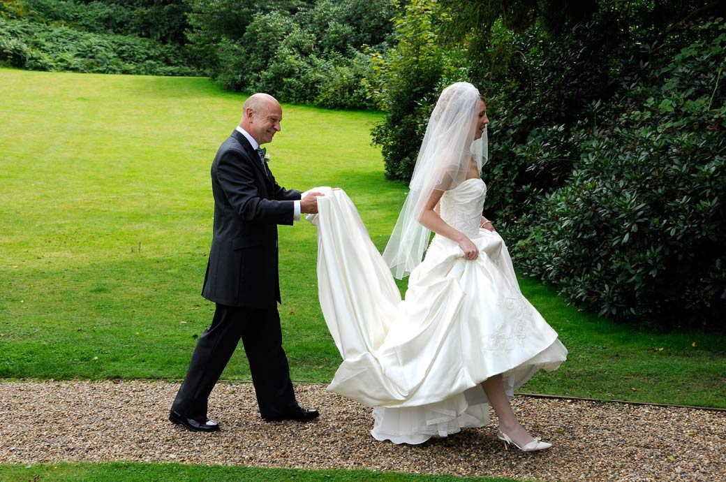 Father of the Bride walks behind his daughter holding up here dress in this wedding picture taken on the way to the Turtle Room at Surrey wedding venue Wotton House Dorking