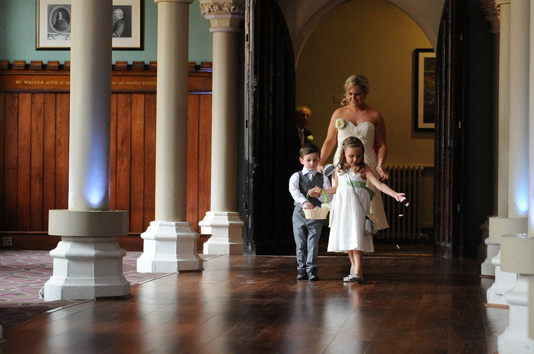 Wedding photograph of a Flowergirl and pageboy dropping petals down the aisle in the magnificent Old Library at Wotton House in Surrey Dorking