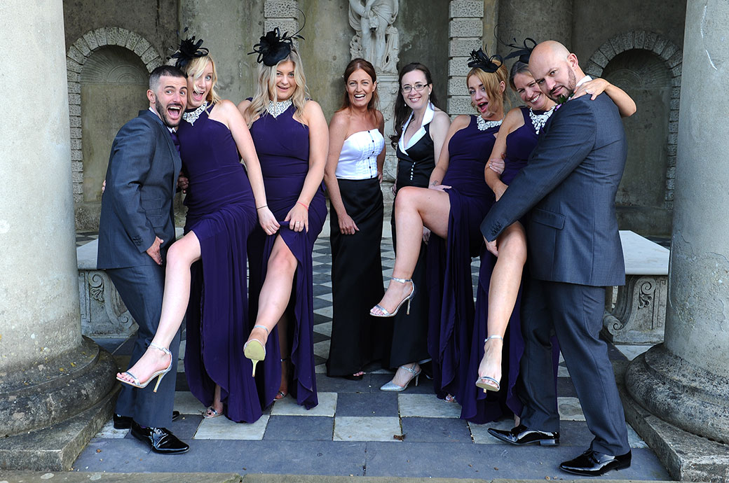 Grooms and their glamorous bridesmaids get a bit saucy as they strike a pose in the Roman Temple at Wotton House a Surrey wedding venue in Dorking