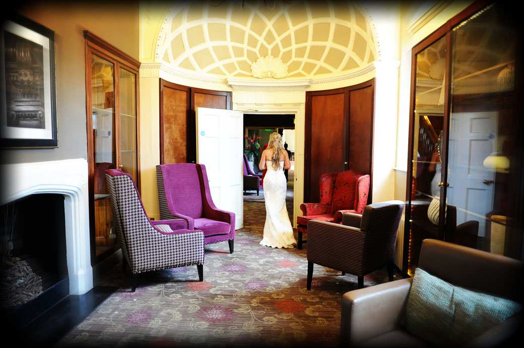 Bride looking glamorous in her  beautiful wedding dress as she leaves the lounge area at Wotton House in Surrey to enter the Old Library for the wedding breakfast