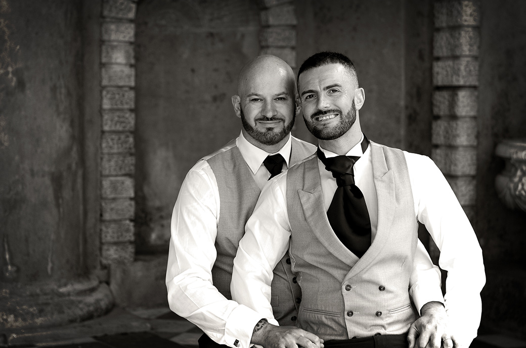 Lovely relaxed and romantic wedding photograph of the two Grooms at Surrey wedding venue Wotton House taken as they sit together in the Roman Temple