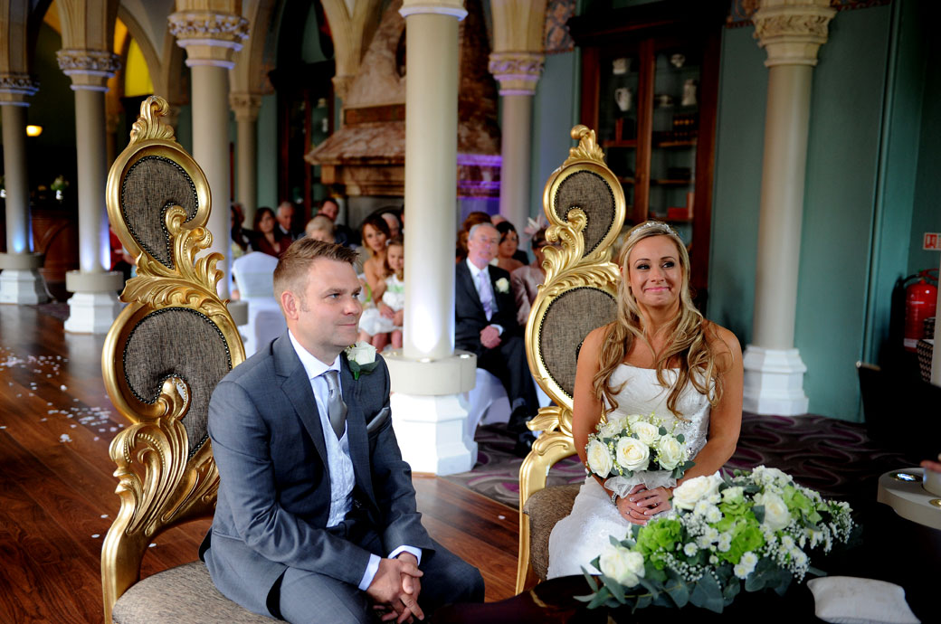 Happy and smiling the Bride and Groom sit in the golden thrones in the Old Library at Surrey wedding venue Wotton House as they listen to the registrars introduction