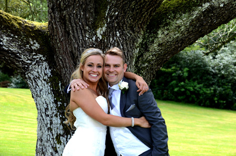 Big smiles and hugs for the very happy Bride and Groom as they stand in front of a tree on the lawn at the ever popular and award winning Surrey wedding venue Wotton House