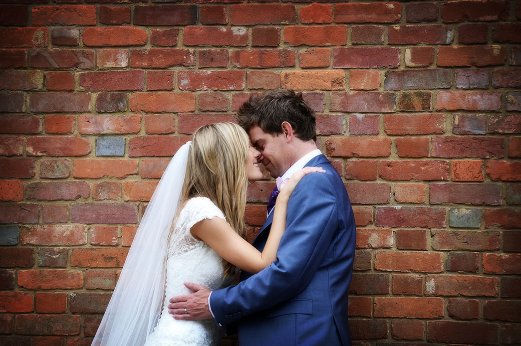 Loving couple share a moment of tenderness as they hug each other by a wall at the front of the award winning wedding venue Wotton House in Dorking Surrey