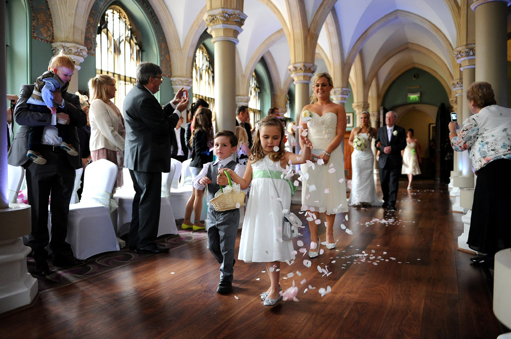 Flowergirl and pageboy leading the wedding party down the aisle as they throw petals down before them captured in this atmospheric Wotton House wedding picture