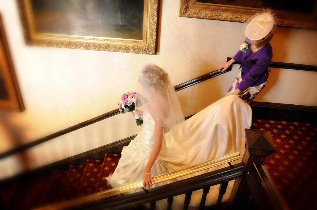 A magical wedding picture of the Mother and Bride descending the stairs at Wotton House, Dorking Surrey captured by Surrey Lane wedding photography