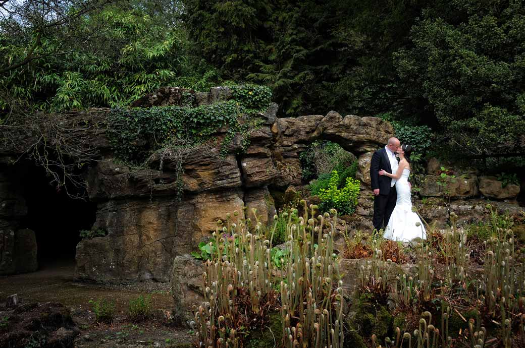 A romantic long distance wedding photograph of the newly-weds kissing in front of the ivy covered Grotto at Wotton House Dorking Surrey wedding venue