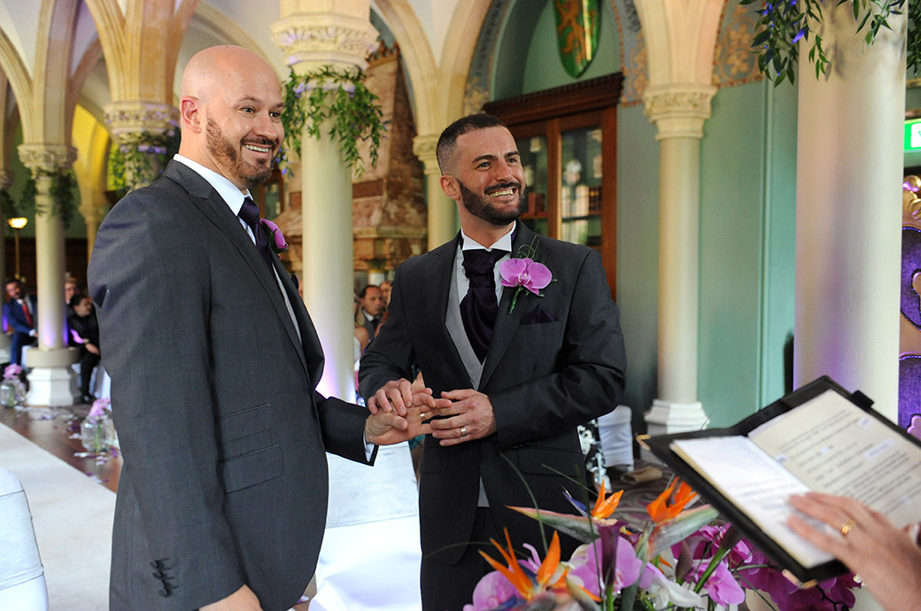 Lovely smiles and overflowing emotions as a groom places the ring on his partner's finger in the atmospheric Old Library at Surrey wedding venue Wotton House in Dorking