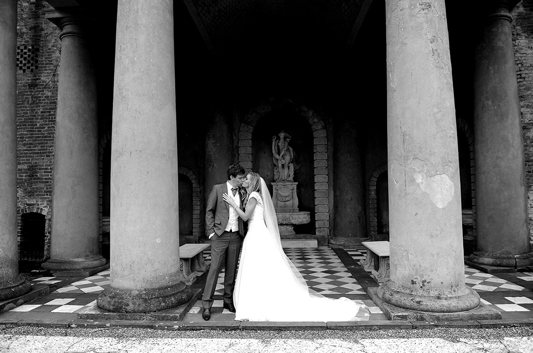 Bride and groom enjoy a romantic kiss in front of the classical columns of the wonderful Roman Temple at Wotton House a wedding venue in Dorking Surrey