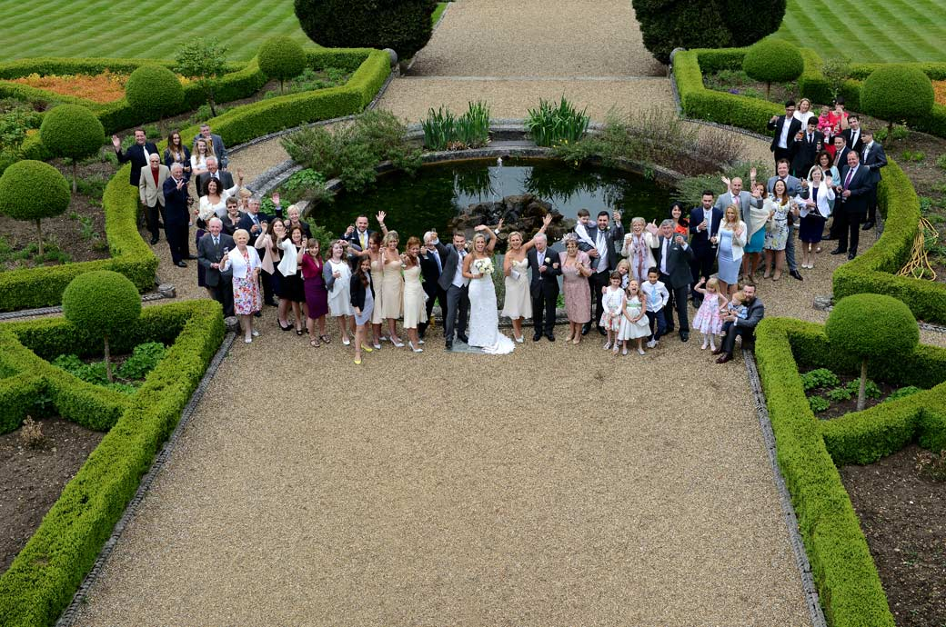 Everyone in this classic  Wotton House wedding photo of everyone waving around the fountain at the Surrey Lane wedding photographer from up high on the temple roof