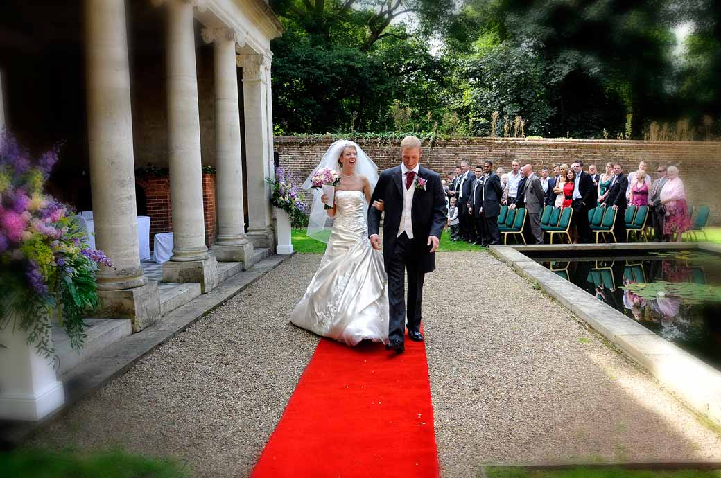 An exuberant Bride and Groom walk the red carpet from the Turtle House as a married couple at Wotton House wedding venue Dorking by Surrey Lane photo