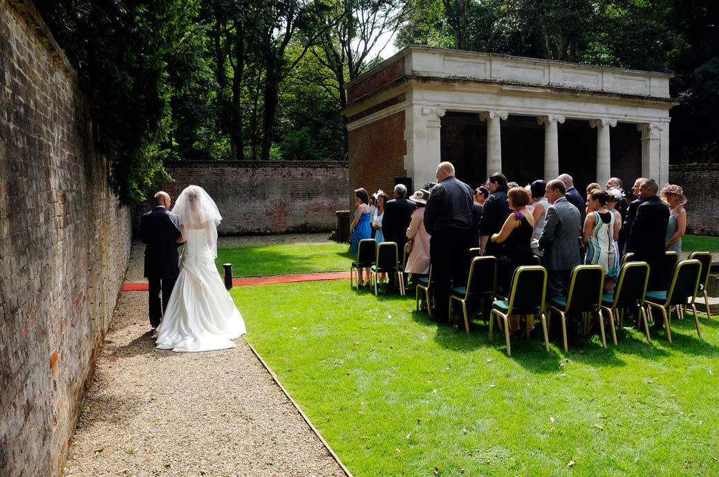 Father with daughter Bride on arm in this wedding photograph taken as they approach the Turtle Room for their open air  wedding ceremony at Wotton House Dorking Surrey