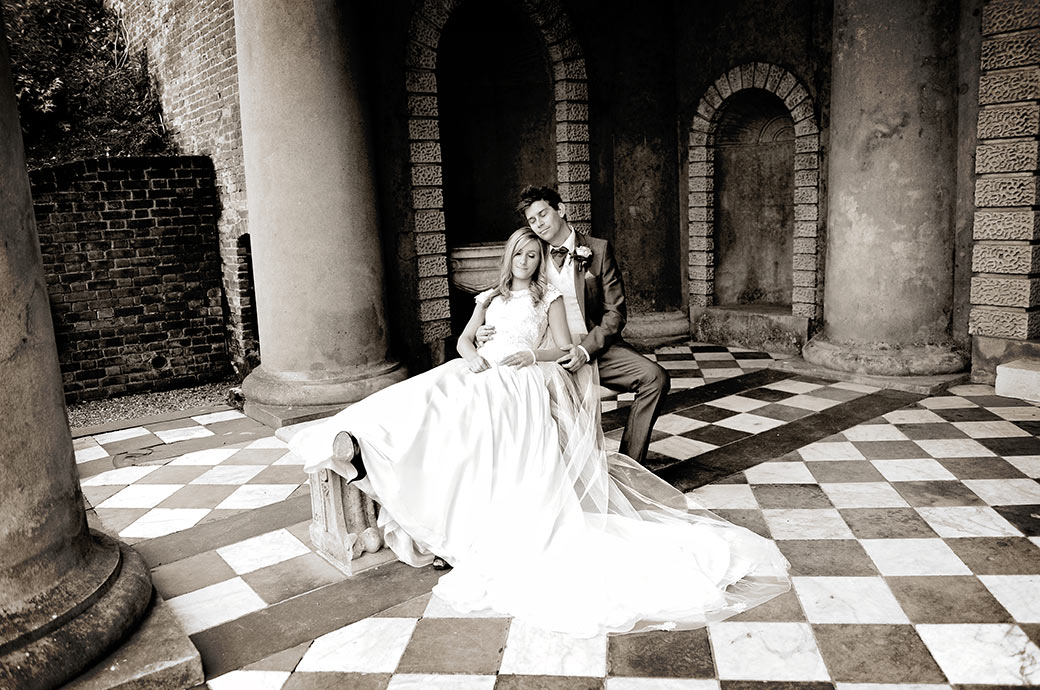 A tired Bride and groom at Wotton House in Dorking Surrey take a moment to close their eyes as they enjoy the peace and tranquillity inside the Roman Temple