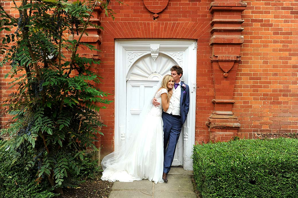 Smiling Bride at Surrey wedding venue Wotton House in Dorking relaxes with her Groom in front of a white door after a romantic walk around the grounds