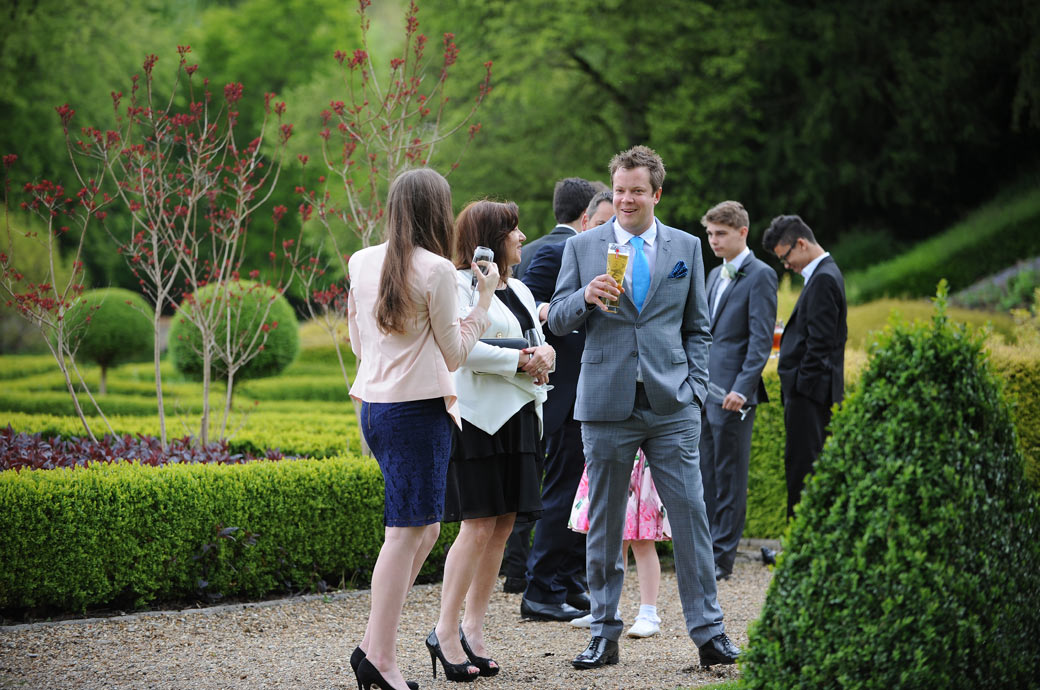 Guests at Surrey wedding venue Wotton House Dorking captured as they enjoy a drink and conversation out in the lovely tranquil grounds