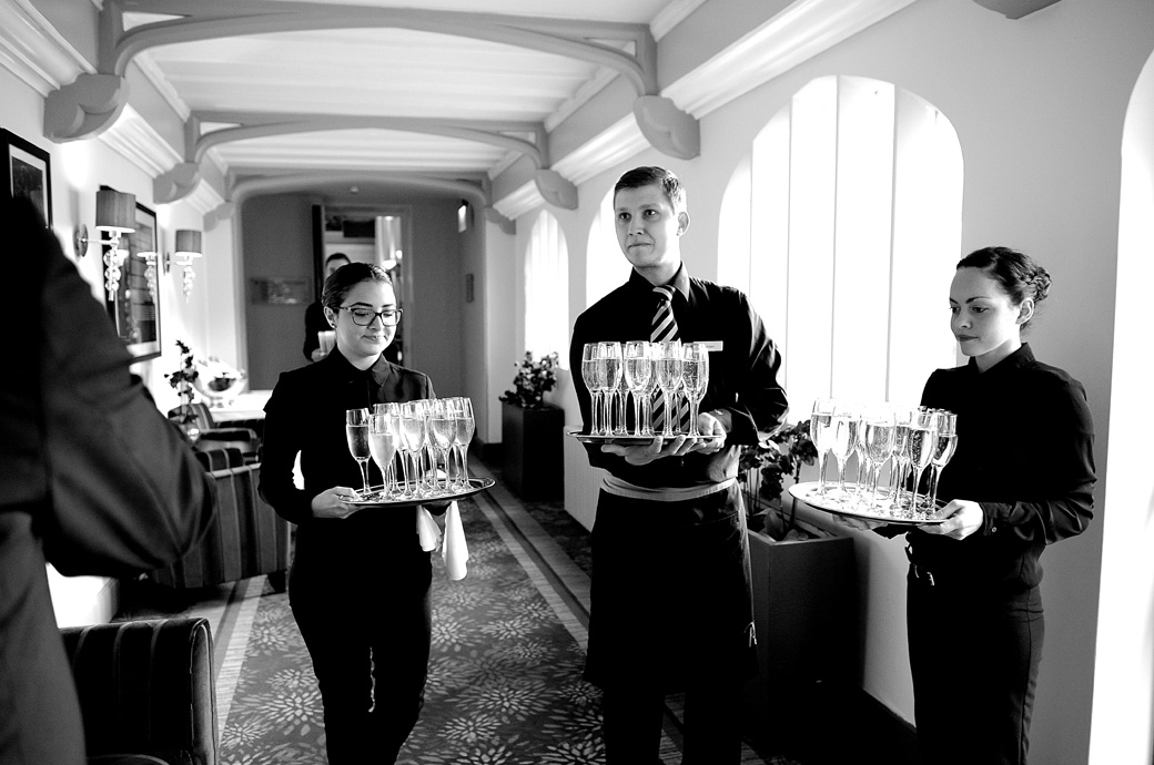 Young Wotton House waiters await the newlyweds and guests with glasses of champagne leading out to the patio and grounds for the marriage celebrations in Surrey