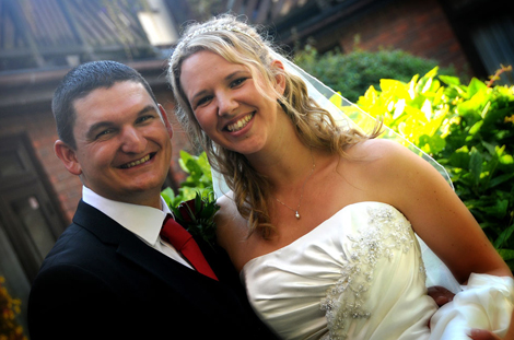 A beaming happy Bride and Groom wedding picture taken as the rain stops and the sun shines at Brook Kingston Lodge Hotel Surrey wedding