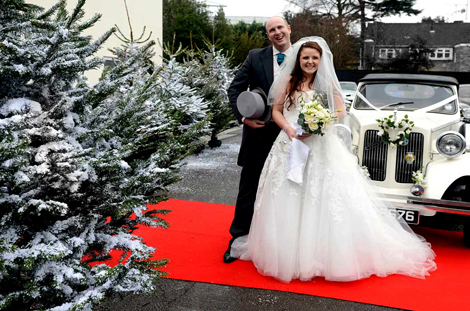 Happy Bride and Groom wedding photo taken on a red carpet next to the wedding car and Christmas tree at Glenmore House in Surbiton Surrey