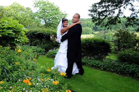 Bride and Groom in front of the striking Nonsuch Mansion wedding photograph taken on the lawn at this fine Surrey wedding venue
